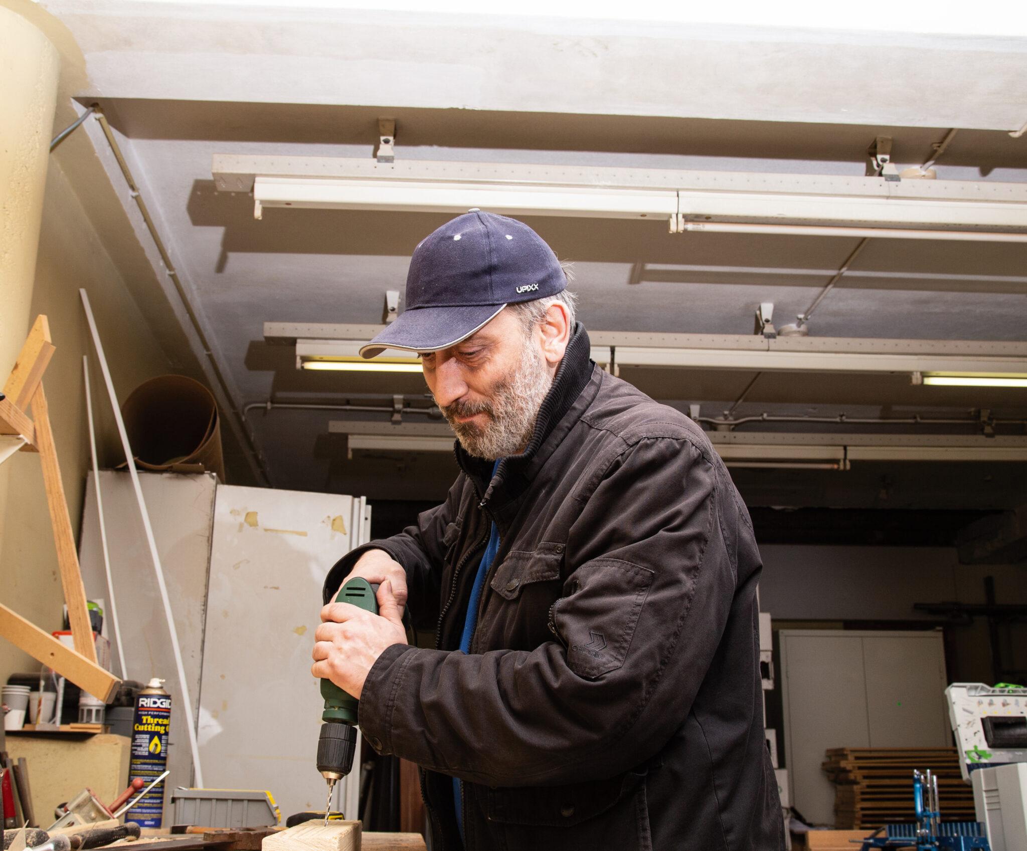 Hier staat een man met blauwe pet in een werkruimte. Hij gebruikt een boor om een gat te maken in een stuk hout. Om hem heen staat gereedschap.