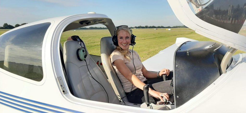 Hier ziet u een blonde, lachende vrouw in een klein vliegtuig. De dame draagt een koptelefoon met microfoon.