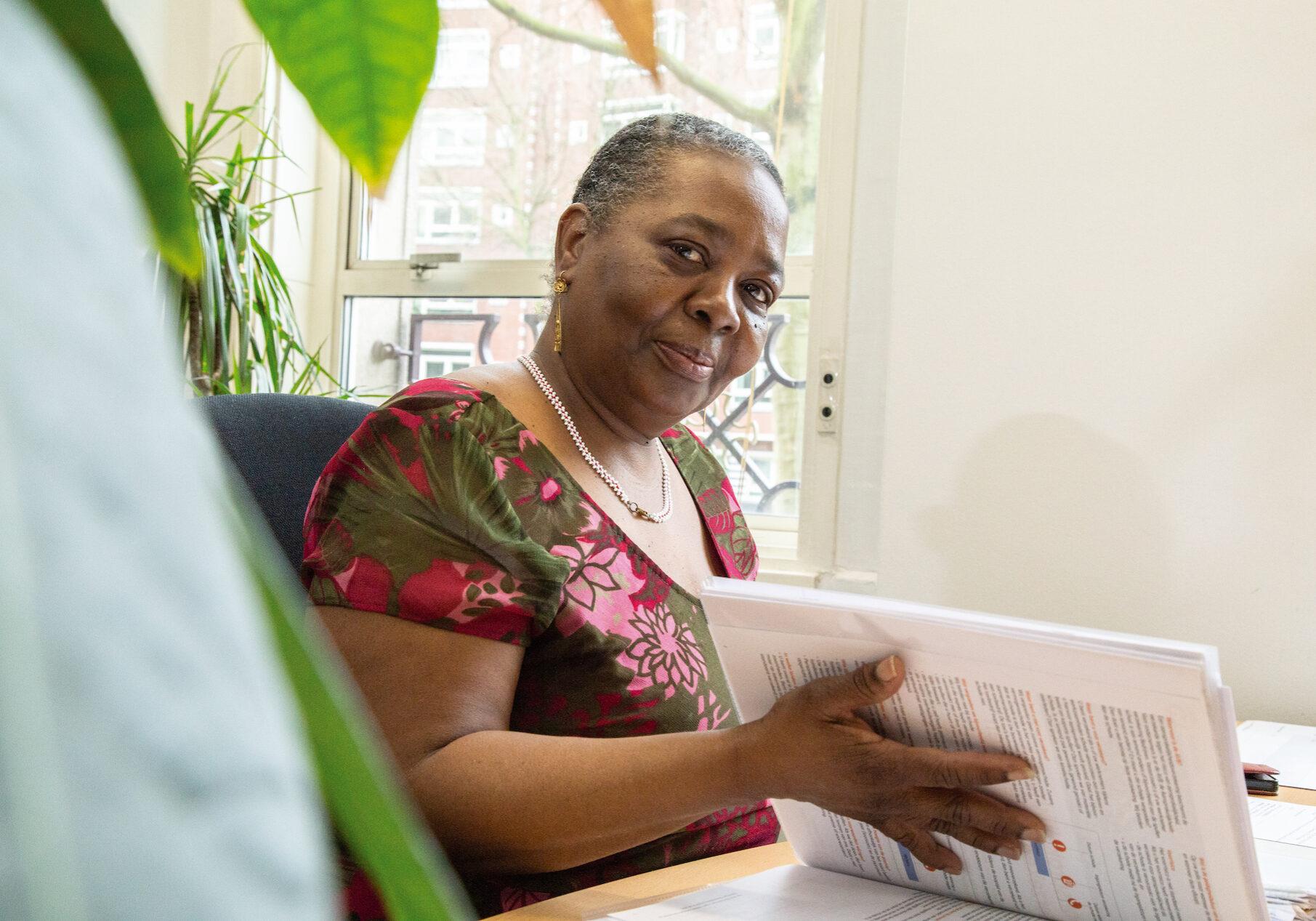 Op deze foto is een dame te zien die een opengeslagen map vasthoudt. De vrouw kijkt in de camera en draagt een gebloemde blouse.