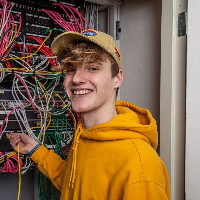 Hier staat een lachende jongeman in een oranje trui. Hij werkt in een patchkast met bedrading.